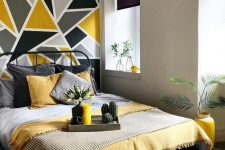 a bold modern bedroom with dove grey walls, a black forged bed, grey and yellow bedding and a geometric grey and mustard wall