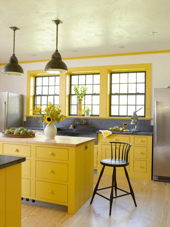 a bright farmhouse kitchen with bold yellow cabinets and window frames, grey stone countertops and a large sink