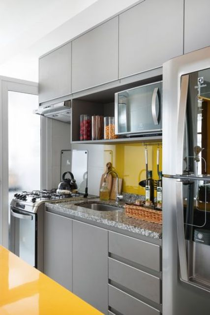 a bright minimal kitchen with sleek grey cabinetry, a bold yellow backsplash and a kitchen island to contrast