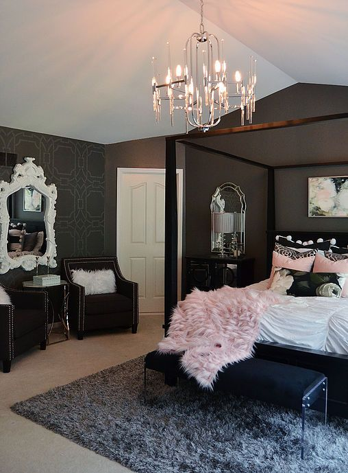 a chic and refined bedroom with black walls, a black bed and other sitting furniture, a catchy crystal chandelier and pink bedding
