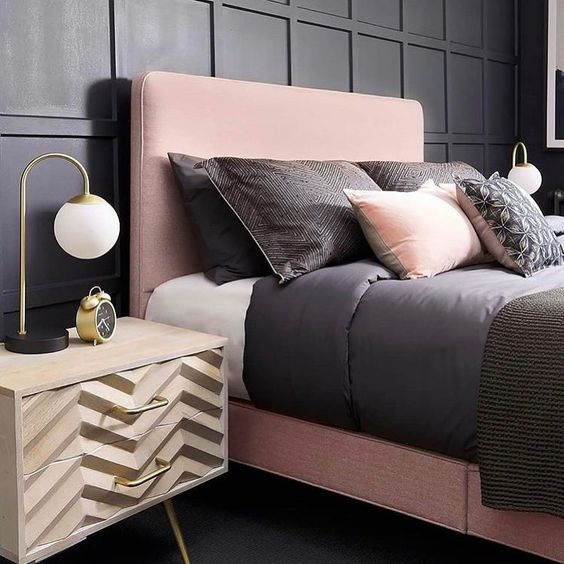 a chic bedroom with black paneling, a pink bed, black and pink bedding and chevron nightstands plus touches of gold