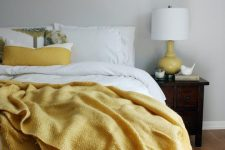a chic bedroom with dove grey walls, white and sunny yellow linens, a mustard lamp and chic touches