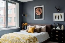 a chic bedroom with graphite gray walls, a brown bed, mismatching nightstands, yellow linens and printed textiles