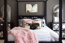 a chic grey bedroom with black furniture, mirrored nightstands, blush and black bedding and layered rugs