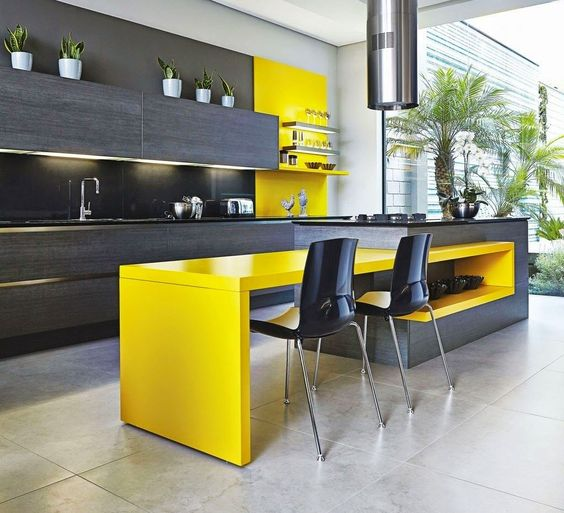 a chic kitchen with dark grey wooden cabinetry, a matching kitchen island with a bright yellow table and a backsplash