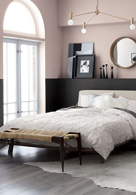 a chic modern bedroom with color block blush and black walls, a neutral bed, a mid century modern chandelier and a woven bench