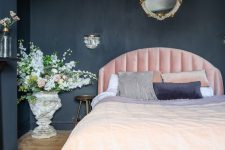 a chic moody bedroom with black walls and a chest for storage, a light pink bed, refined lighting and blooms