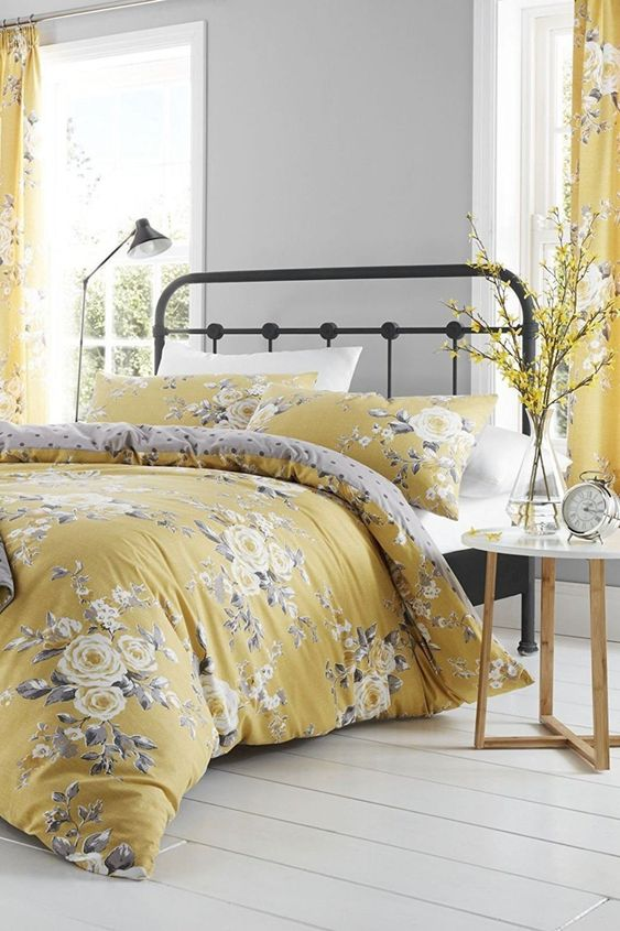 a chic romantic grey and yellow bedroom with dove grey walls, a metal bed, grey and yellow floral textiles and blooming branches