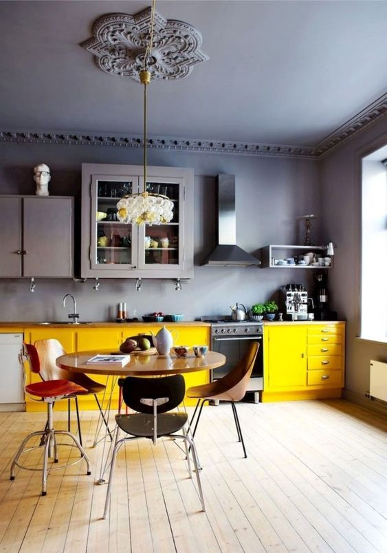 a contrasting and moody kitchen with grey walls and a ceiling, upper cabinets and lower yellow ones, mismatching chairs
