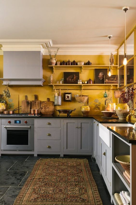 a cozy eclectic kitchen with warm yellow walls and grey cabinets, black countertops and artworks on the shelves