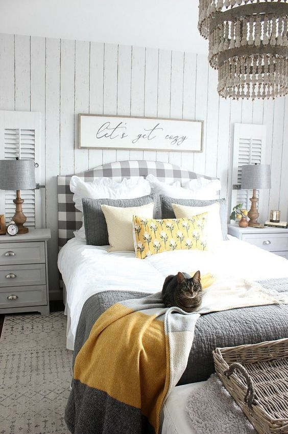 a cozy farmhouse bedroom with a grey plaid bed, dove grey nightstands and lamps, grey and yellow bedding