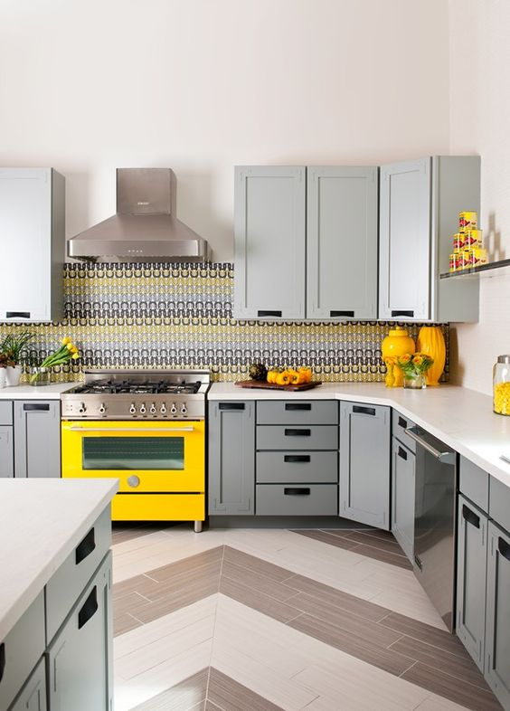 a cozy kitchen with dove grey cabinets, a bright yellow cooker and accessories plus a mosaic tile backsplash