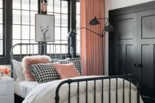 a cute pink, black and white bedroom with black paneling, a forged bed, pink curtains and pillows for a chic look