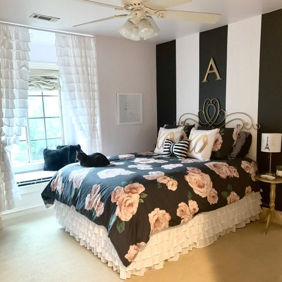 a glam and refined bedroom with a striped accent wall, black floral bedding, white ruffle curtains and exquisite furniture