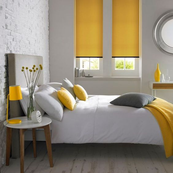 a minimalist grey and yellow bedroom with simple and minimal furniture, a grey bed, yellow linens and neutral textiles