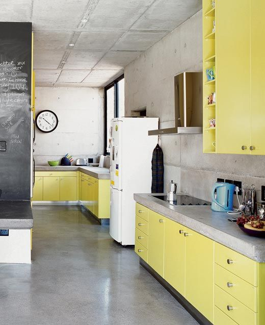 a minimalist light yellow kitchen with concrete countertops and walls is a simple and bright space that looks contrasting