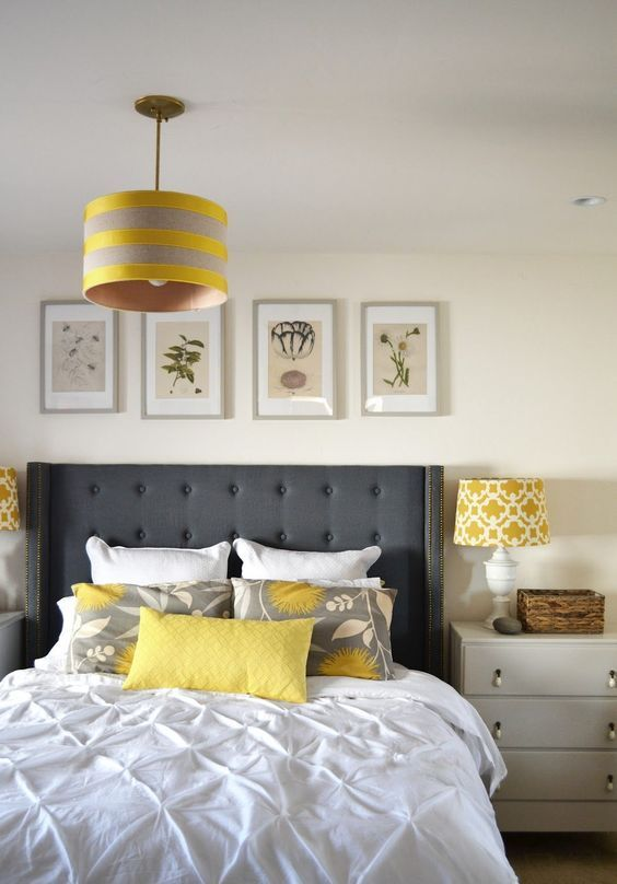 a modern bedroom in off-white and creamy, with a graphite grey bed, touches of yellow and a botanical gallery wall