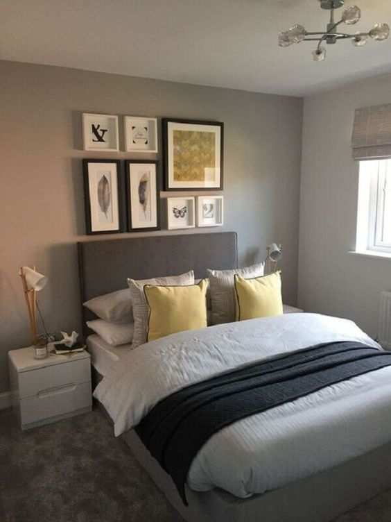 a modern dove grey bedroom with a grey bed, grey and yellow linens, a grey and yellow gallery wall