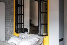 a modern industrial bedroom with light grey walls, a grey brick wall, a yellow zone with a window and a yellow bed with grey bedding