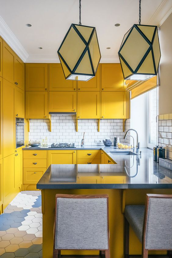 a mustard kitchen with grey stone countertops and grey stools, a white subway tile backsplash anbd geometric pendant lamps