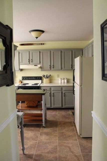 a peaceful kitchen with pale yellow walls, traditional grey cabinets with paneling and a metal and wood kitchen