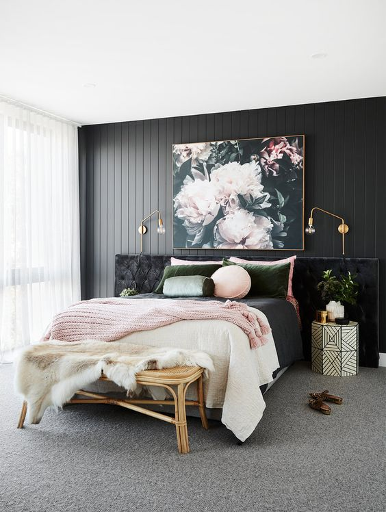 a refined bedroom with a black wooden accent wall, a black upholstered bed, pink and green bedding and a beautiful floral artwork