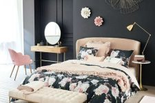 a refined bedroom with black walls, a tan bed and a creamy bench, a pink chair and floral bedding