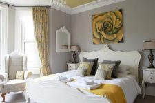 a refined bedroom with dove grey walls, a pale yellow ceiling, elegant creamy furniture, a crystal chandelier and touches of mustard