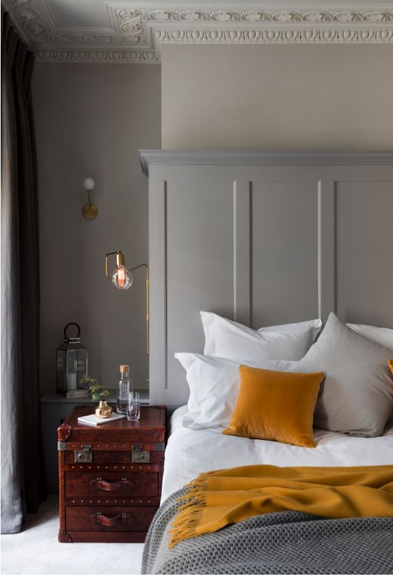 a refined bedroom with dove grey walls, molding, a vintage chest as a nightstand, mustard linens and touches of gold