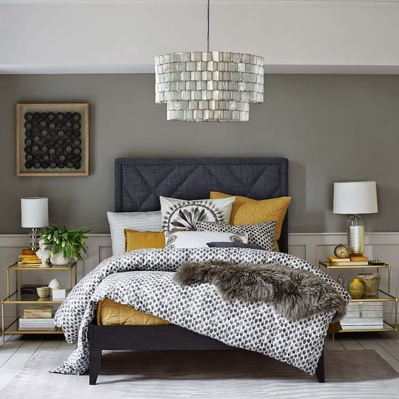 a shiny and elegant bedroom with grey walls, white paneling, a graphite grey bed, a shiny chandelier, gold frame nightstands and mustard bedding