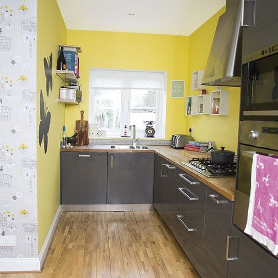 a simple modern kitchen with yellow walls, glossy grey cabinets and wooden countertops for a contrasting look
