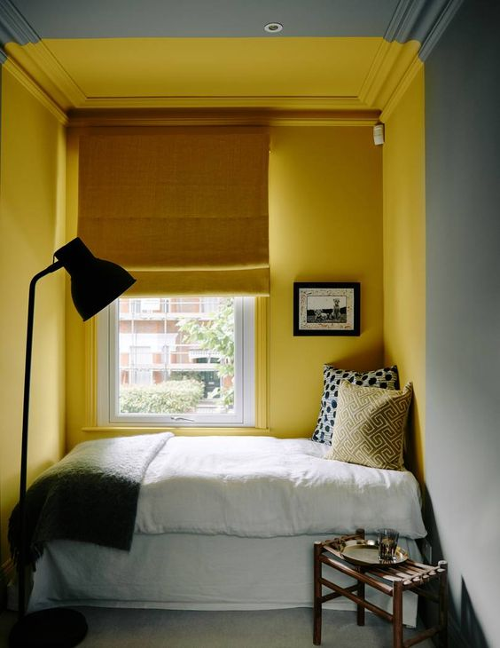 a small and cozy bedroom with grey walls and a sunshine yellow nook with a bed, a mustard curtain and grey and yellow bedding