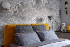 a small bedroom with a grey cloud wallpaper wall, a mustard upholstered bed and accessories, grey and white bedding