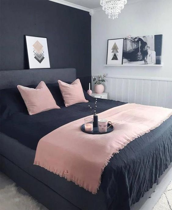 a small modern bedroom with a black statement wall, a black bed, pink and black bedding and a crystal chandelier