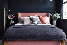 a small modern bedroom with black wooden walls, a pink bed and grey and pink bedding and greenery and blooms