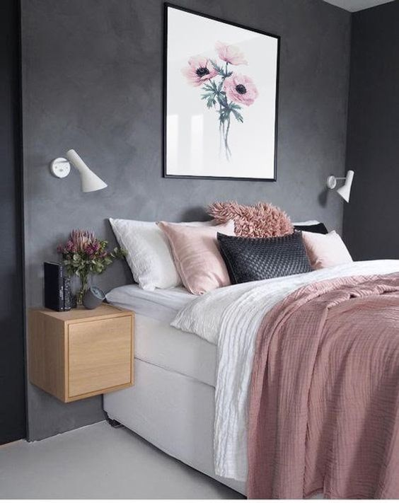 a stylish and simple bedroom with black walls, a white bed, pink and black bedding, floating nightstands and sconces