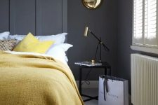 a stylish bedroom with graphite grey walls, simple and elegant furniture, lemon yellow textiles and gold touches