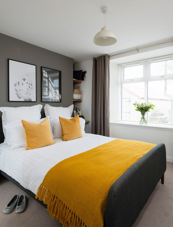a stylish contemporary bedroom with grey walls and a floor, a graphite grey bed, mustard linens and taupe curtains