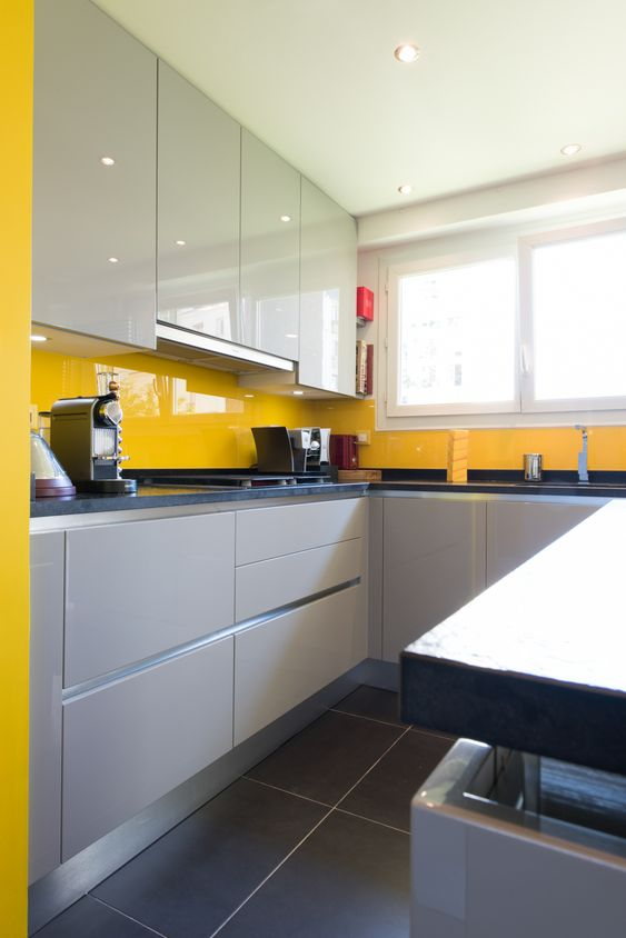 a stylish minimalist kitchen with white and dove grey cabinetry and a sunny yellow sleek glass backsplash stands out