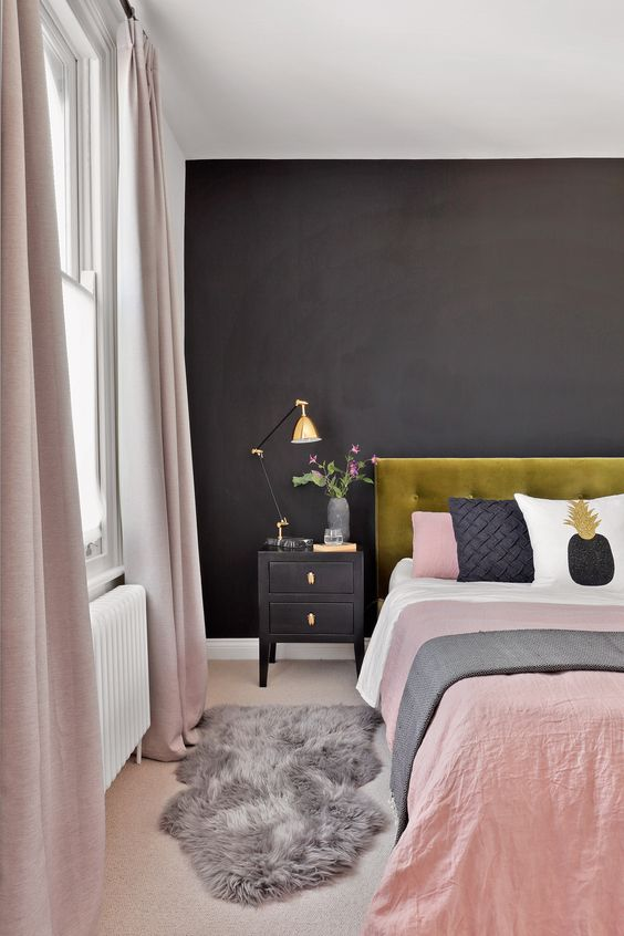 a stylish modern bedroom with a black statement wall, a mustard velvet bed, black nightstands, blush linens and gold touches