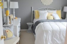 a traditional bedroom with grey walls, chic white furniture, grey and yellow bedding and touches of bright yellow