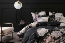 a very refined bedroom with black walls, paneling, black and pink floral bedding, a blush chair and a pendant lamp