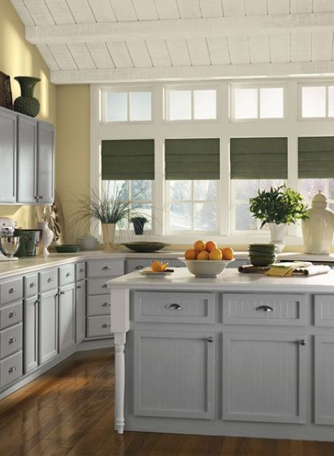 a welcoming farmhouse kitchen with pale yellow walls, stylish vintage-inspired cabinets in grey and green shades on the window
