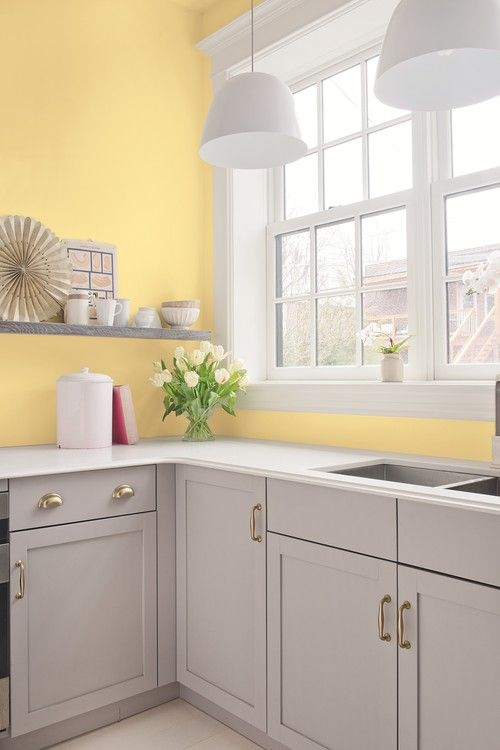 an airy kitchen with light yellow walls, dove grey cabinets and shelves, white pendant lamps and countertops