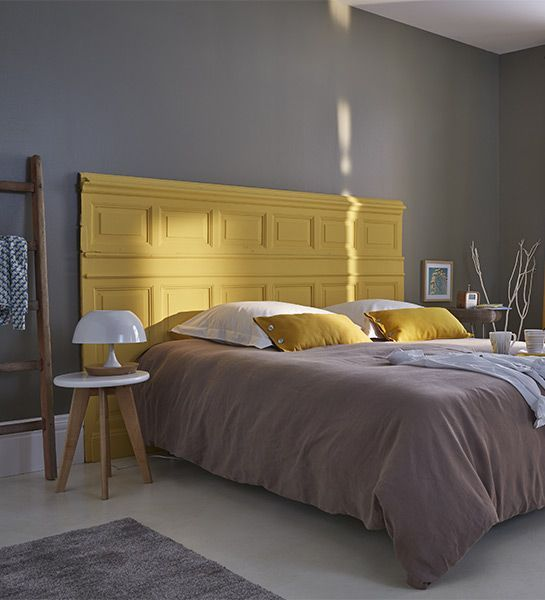 an eclectic bedroom with grey walls, a yellow paneled bed, grey and mustard bedding is very dreamy