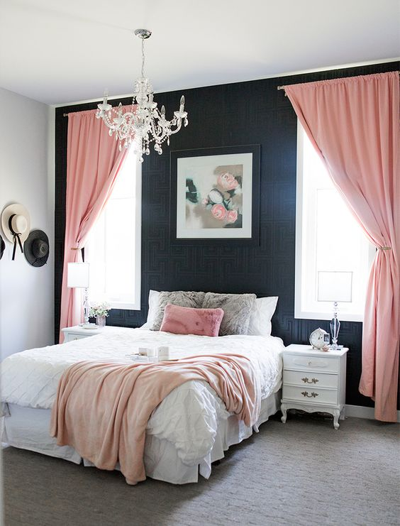 an elegant bedroom with black printed wallpaper, refined white furniture, pink textiles and a crystal chandelier