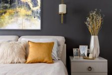 an elegant bedroom with graphite grey walls, creamy furniture, white and mustard linens and a 3D vase