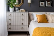 an elegant mid-century modern bedroom with graphite grey walls, neutral furniture, shiny and bright touches and yellow and white bedding