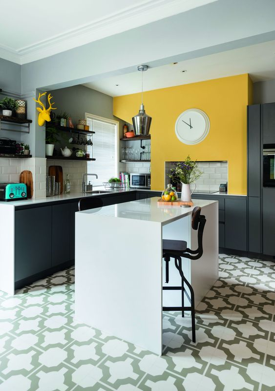 an elegant modern kitchen with graphite grey cabinets, a sunny yellow wall and a white kitchen island