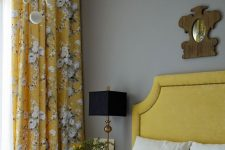 an elegant vintage-inspired bedroom with light grey walls, a mustard bed, mustard floral curtains, a chic chandelier and grey and mustard bedding